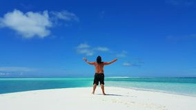 P01718 Maldives white sandy beach young man standing on sunny tropical paradise island with aqua blue sky sea ocean 4k. Maldives white sandy beach young man Stock Images