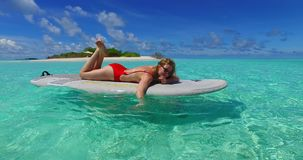Maldives white sandy beach 1 young woman paddleboard rowing on sunny tropical paradise island. With aqua blue sky sea water ocean 4k stock video footage
