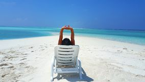 Maldives white sandy beach young woman relaxing on sunbed on sunny tropical paradise island with aqua blue sky. Sea ocean 4k Royalty Free Stock Photography