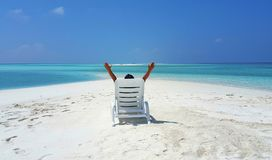 Maldives white sandy beach young woman relaxing on sunbed on sunny tropical paradise island with aqua blue sky. Sea ocean 4k Royalty Free Stock Photos