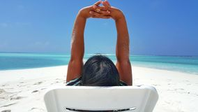 Maldives white sandy beach young woman relaxing on sunbed on sunny tropical paradise island with aqua blue sky. Sea ocean 4k Stock Photo