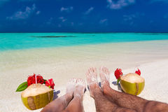 Maldives, women and man legs with coconuts Royalty Free Stock Photos