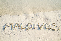 'Maldives' written in sand. Royalty Free Stock Image