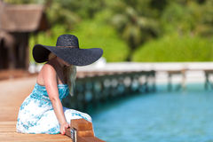 Maldives, a young woman sitting on a bridge in a black hat Stock Photography