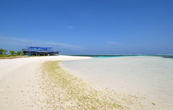 Maldivian beach with white sand. Azure water and old blue boat Stock Image
