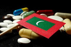 Maldivian flag with lot of medical pills isolated on black background Royalty Free Stock Photography