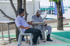 Maldivian militaire mensenzitting met zijn vriend die mobiele telefoons met behulp van Stock Fotografie