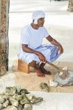 Maldivian pracownik budowlany w krajowym Maldivian odzieżowym obsiadaniu z cioska pobliskim stosem skały fotografia royalty free
