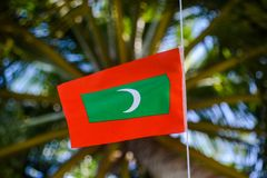 Maldivian red green colour national flag on the rope during beautiful windy day stock photo