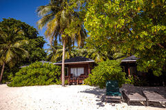 Maldivian resort huts and sunbeds on the beach Stock Images