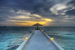 Maldivian sunset. Magic of paradise sunset under umbrella Royalty Free Stock Images