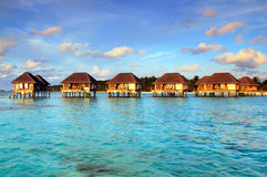Maldivian water bungalows. With blue sky and sea royalty free stock photo