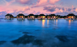 Maldivian water bungalows at dusk Royalty Free Stock Photos