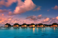 Maldivian water bungalows at dusk Royalty Free Stock Photography