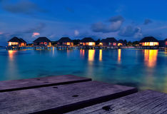 Maldivian water bungalows at dusk. Water bungalows with beautiful twilight sky and sea in Maldives. Long Exposure royalty free stock images