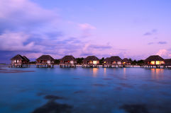 Maldivian water bungalows at dusk. Water bungalows with beautiful twilight sky and sea in Maldives. Long Exposure stock photo