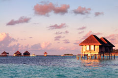 Maldivian water bungalows at dusk. Water bungalows with beautiful twilight sky and sea in Maldives. Long Exposure stock image