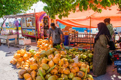 Maldivian women buying coconuts at market place at docks area Stock Photos