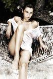 Maldiviana. A girl in a wet white shirt sitting on a tropical beach Stock Photo