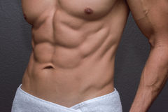 Male abs closeup. Closeup of torso showing muscular lean abdominals and chest of tan Caucasian man with white towel wrapped around waist next to textured gray Stock Photos