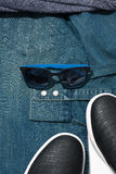 Male accessories. Blue sunglasses laying on a denim men`s shirt near sneakers Stock Photos