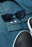 Male accessories. Blue sunglasses laying on a denim men`s shirt near sneakers Royalty Free Stock Images