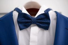 Close-up elegant blue suit with white shirt and blue bow tie, in preparation for a formal event. Male accessories for formal attire, fashion and beauty concept Stock Photography