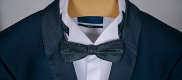 Cropped shot of elegant navy blue suit with white shirt and bow tie. Male accessories for formal attire, fashion and beauty concept, classy groom, sophisticated Stock Images