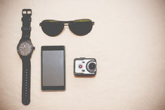 Male accessories in new technologies. Wristwatch, sunglasses, smart phone and very small action camera layed down on floor. Male accessories Royalty Free Stock Photo