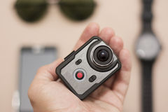 Male accessories in new technologies. Wristwatch, sunglasses, smart phone and very small action cameraas part of new male accessories. Action camera in hand Stock Images