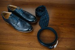 Black leather shoes, golden watch, wooden bow tie and belt stand. Male accessories. Shoes with tie and cuff Stock Images