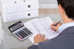 Male accountant calculating invoices. Business man accountant calculating invoices in office Stock Photography