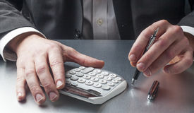 Male accountant couting margins and costs at his desk Royalty Free Stock Images