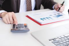 Male accountant using calculator and discussing financial reports. royalty free stock image