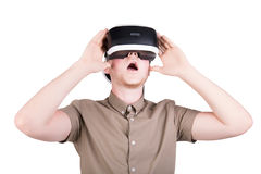 A male action in virtual reality helmet, isolated on a white background. A smartphone using with VR headset. Close-up portrait of a surprised or scared young Stock Photo
