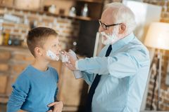 Happy senior man applying shaving foam. Male activity. Happy positive senior men looking at his grandchild and applying shaving foam on his cheeks while teaching Royalty Free Stock Photo