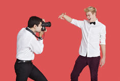 Male actor being photographed by paparazzi over red background Royalty Free Stock Images