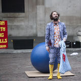 Male actor in a blue suit and yellow rubber dog shows performance at Covent Garden Stock Photography