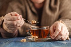Male add sugar in hot tea Stock Photography