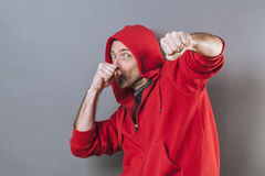 Male adolescence concept for countering middle aged man. Male adolescence concept - countering middle aged man wearing a red hooded sweater playing rapper with Royalty Free Stock Photography