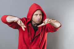Male adolescence concept for hypnotizing middle aged man. Male adolescence concept - hypnotizing middle aged man wearing a red hooded sweater playing rapper with Stock Images