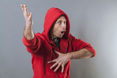 Male adolescence concept for singing middle aged man. Male adolescence concept - singing middle aged man wearing a red hooded sweater playing rapper with fun Stock Images