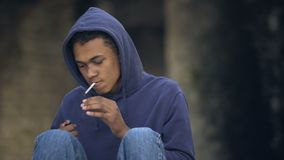 Male adolescent hoodie rolling and smoking joint, harmful nicotine puff, danger. Stock footage stock video
