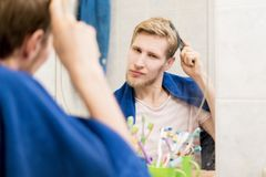 Male adult comb hair in bathroom looking in the mirror with a towel. Male adult comb hair in bathroom looking in the mirror with towel Stock Images