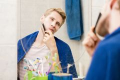 Male adult comb hair in bathroom looking in the mirror with a towel. Male adult comb hair in bathroom looking in the mirror with towel Royalty Free Stock Photo