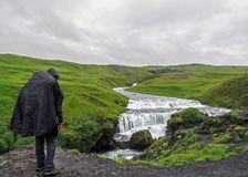 Male adult hiker adventurer hiking in raincoat back standing outdoor looking at waterfall in Laugaveur trek in stunning icelandic stock photography