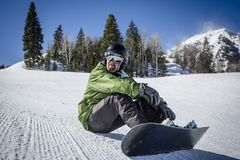 Male adult snowboarder resting on a groomed snow hill Stock Photography