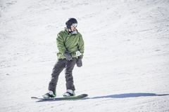 Male adult snowboarder riding down a groomed snow hill. A beautiful day on the slopes having fun Royalty Free Stock Image
