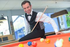 Male adult standing with cue playing billiard royalty free stock image