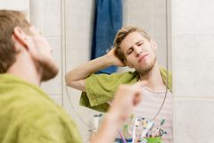 Male adult stretching in front of mirror in the bathroom in morning royalty free stock images